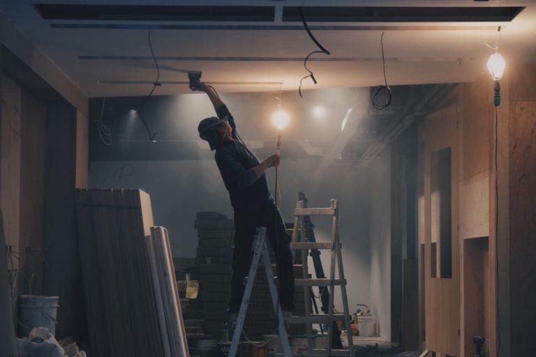 Homme travaillant dans son sous-sol pour isoler sa demeure et éviter la déperdition de chaleur