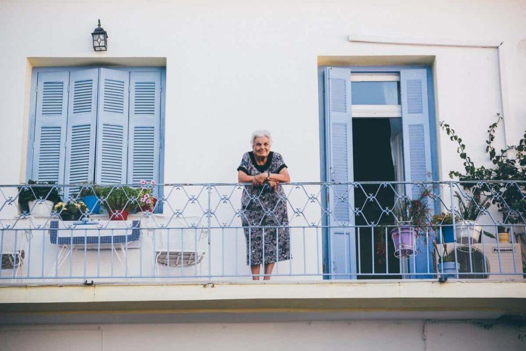 Personne âgée au balcon de son appartement